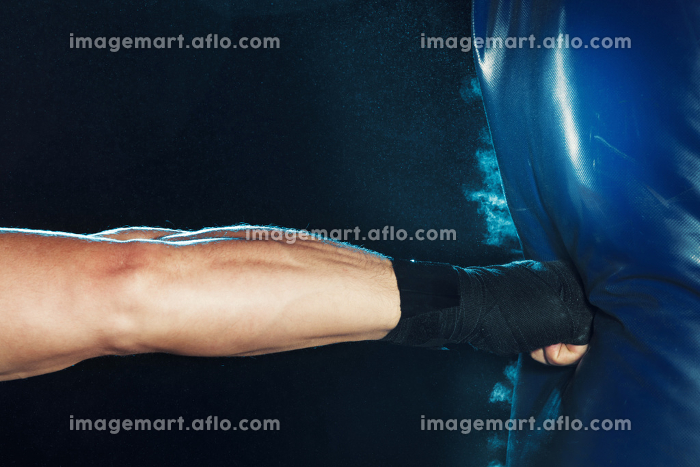 Male boxer boxing in punching bag with dramatic edgy lighting in a dark studioの販売画像