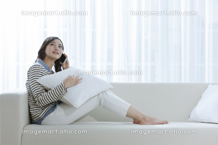 ソファーで電話する女性の販売画像