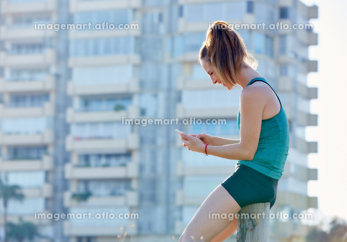 Runner girl having a rest and using smartphone telephone outdoor building parkの販売画像