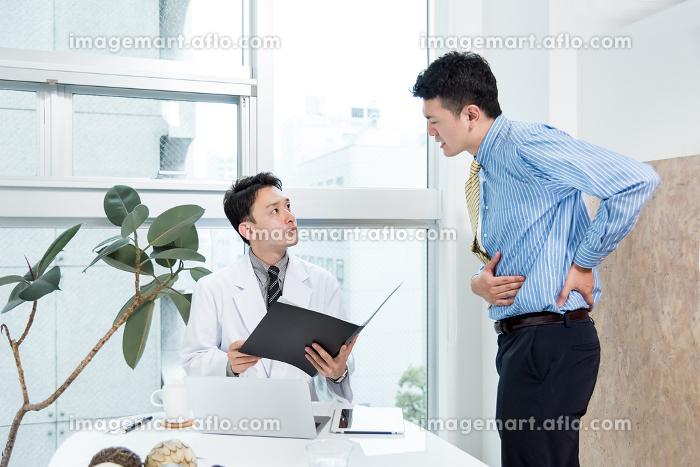 腹痛を訴える男性と診察をする医者の販売画像