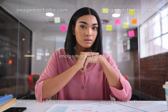 Mixed race businesswoman sitting at desk while having a video call. independent creative design business.の販売画像