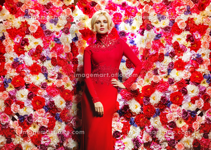 Blond slim lady over the flower wall