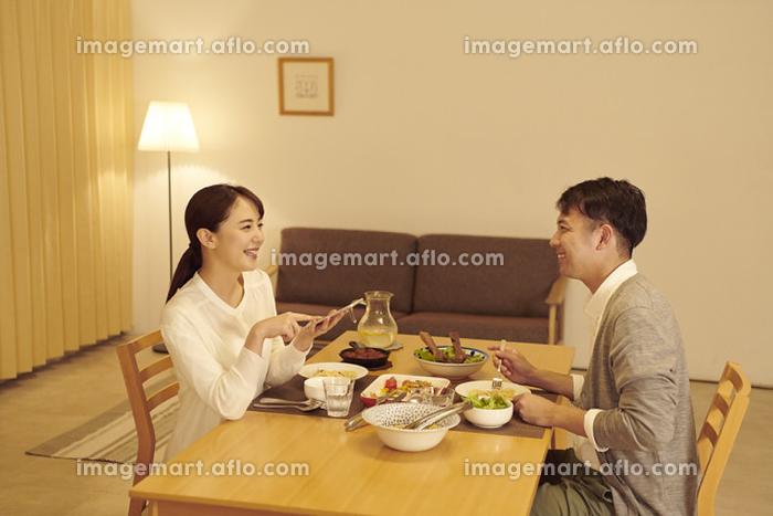スマートフォンをリモコン代わりに使う日本人女性の販売画像