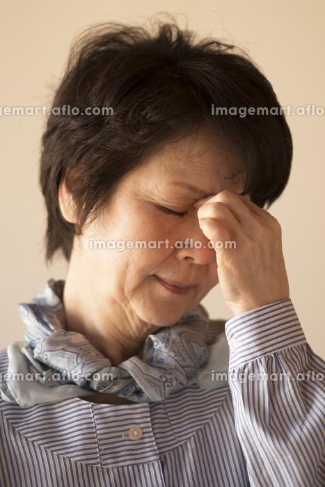 目の疲れに悩むシニア女性