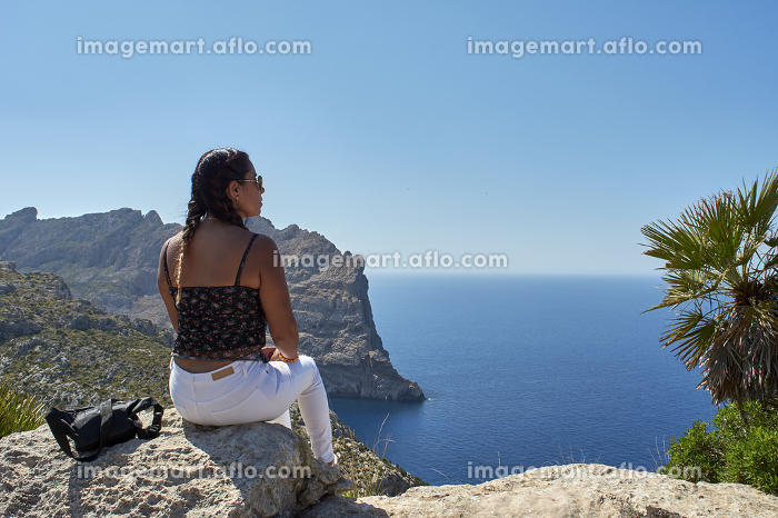 Latin woman, with long wavy brown hair on a spring day wearing sunglasses, in Cape de Formentor, Mallorca, Balearic islands, Spain,の販売画像