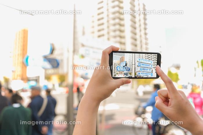 東京の街中でスマートフォンをかざすの販売画像