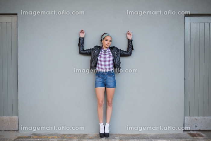 Sexy woman posing on a grey wall and looking at cameraの販売画像