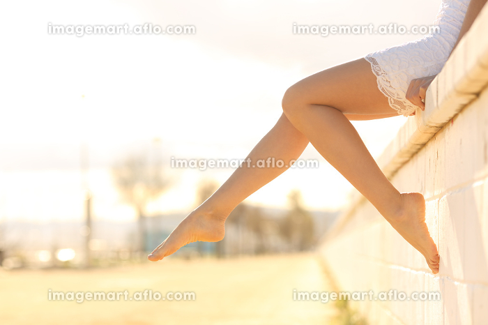 Perfect woman waxed legs outdoors at sunsetの販売画像