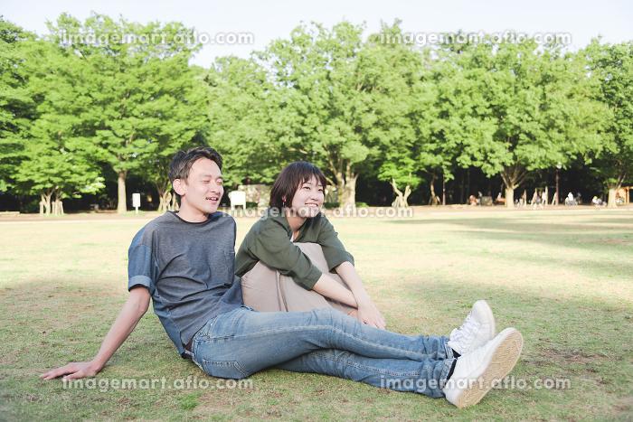 芝生に座る若いカップル(リラックス・公園)の販売画像