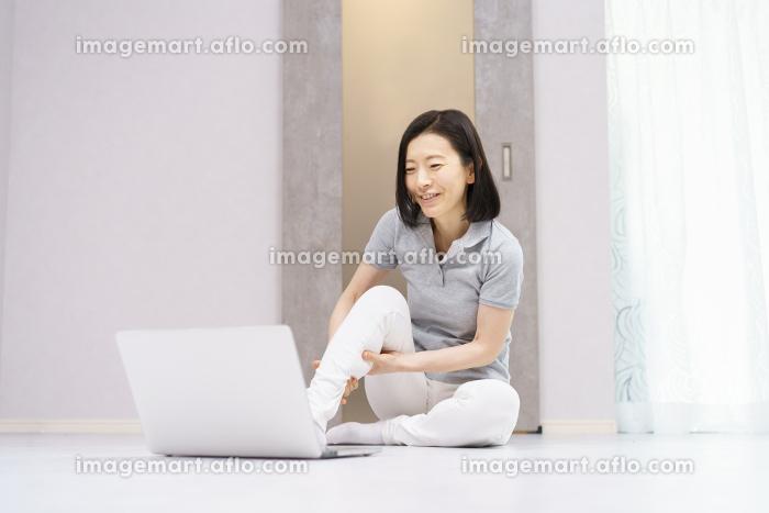 パソコンを見ながら軽い運動をする女性(40代、50代イメージ)の販売画像