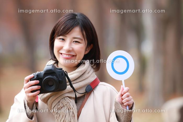 一眼レフカメラと〇札を持つ女性の販売画像