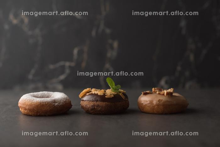 Three donuts on dark stone backgroundの販売画像