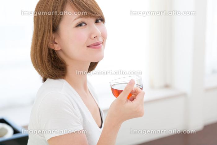 部屋でお茶を飲む女性の販売画像