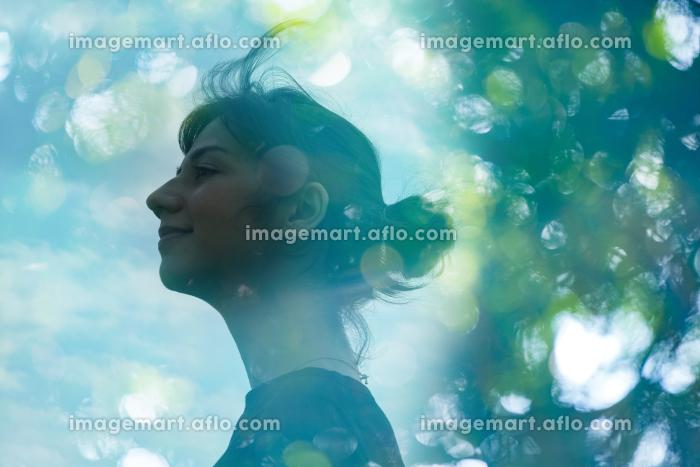 エコロジーイメージ・女性の横顔とアウトフォーカスで撮影した森の合成CGの販売画像