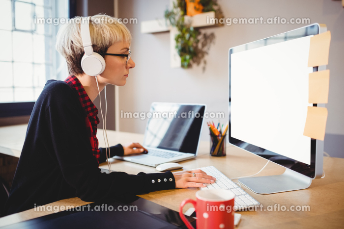 Female graphic designer working on computer and laptop