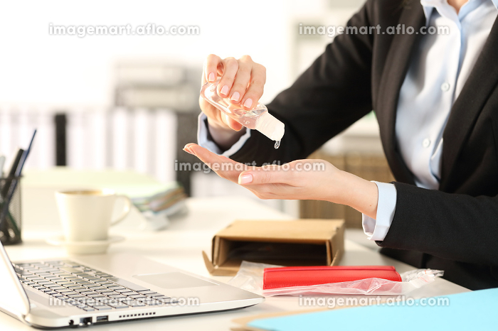 Business woman with opened package sanitizing handsの販売画像