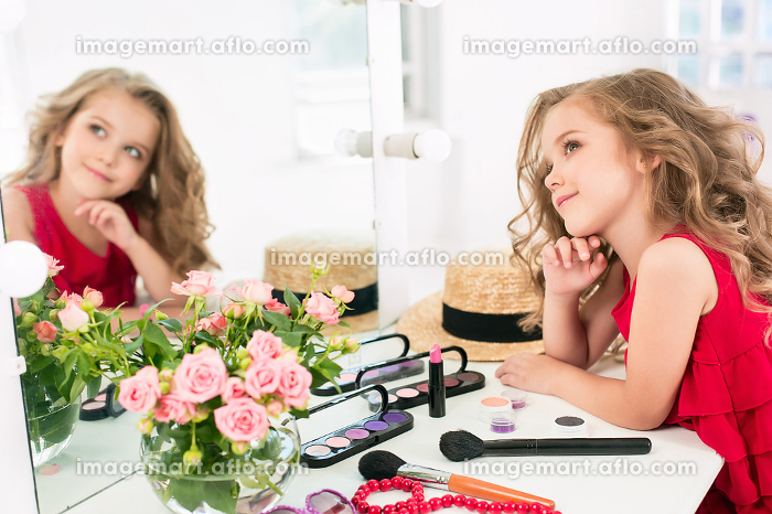 A little girl with cosmetics. She is in mother's bedroom, sitting near the mirror.の販売画像