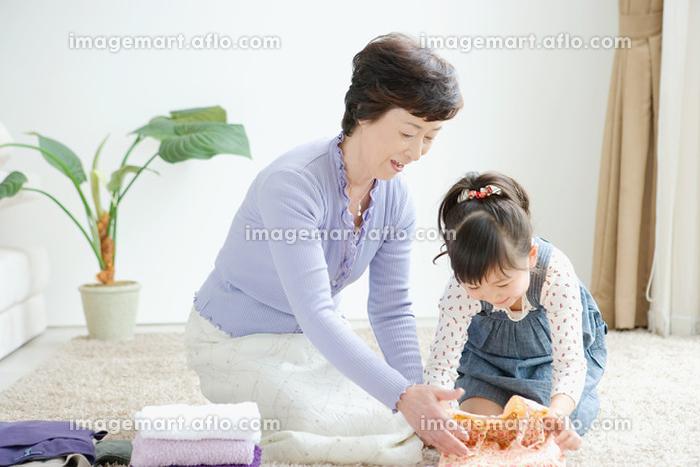洗濯物をたたむ祖母と孫の販売画像