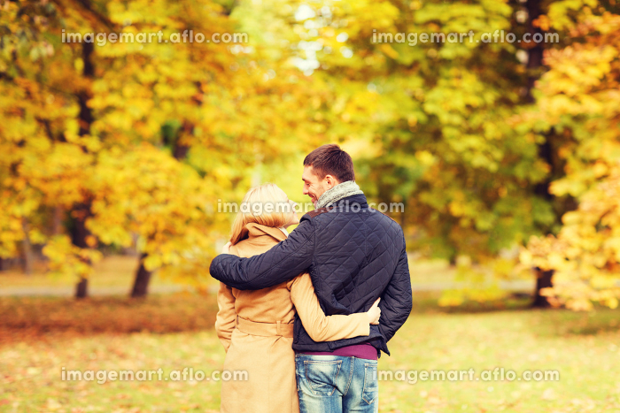 smiling couple hugging in autumn park from back