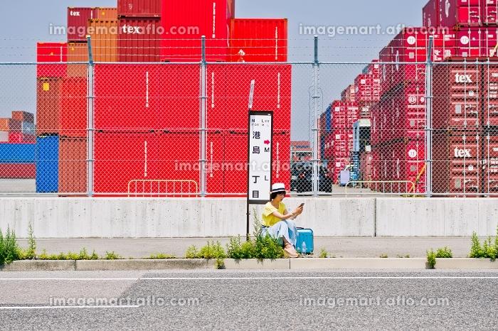 スマホを見ながらバス停でバスを待つ女性