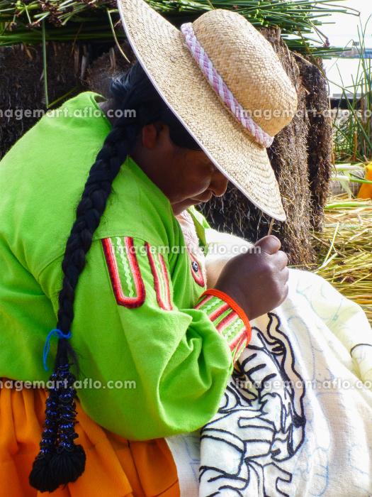 ペルー・チチカカ湖の浮島ウロス島にて編み物をするインディヘナの女性の販売画像