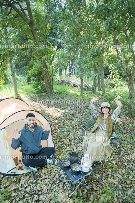 キャンプで記念写真を撮る男女の販売画像