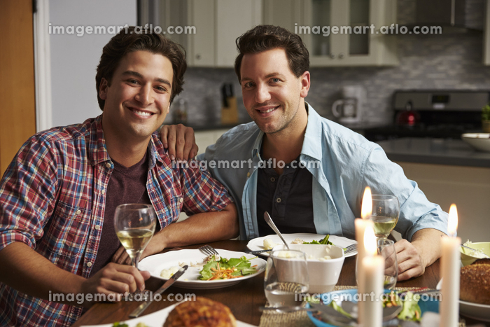 Male gay couple at home for a romantic dinner look to cameraの販売画像