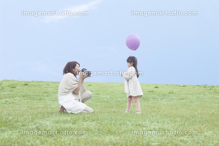 芝生で写真撮影をする母と子の販売画像