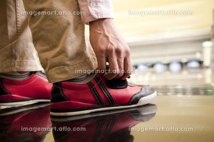 ボウリングシューズを履く男性の足元の販売画像