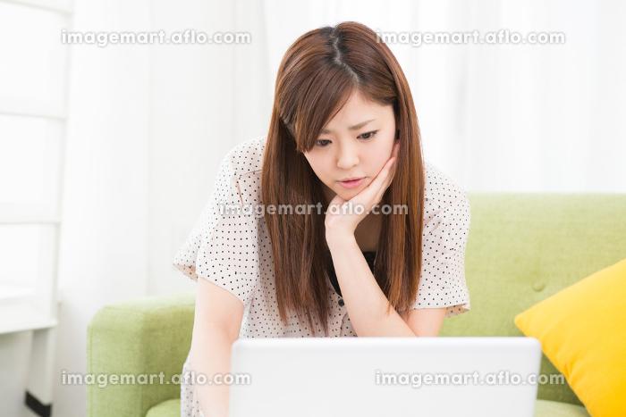 部屋でパソコンを見る女性 考えるの販売画像