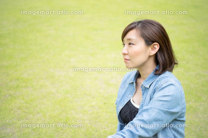 屋外で真剣な眼差しをする女性の販売画像