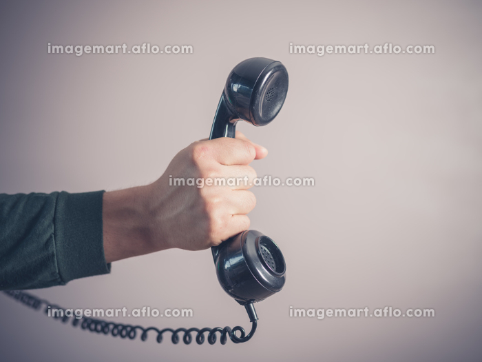 The hand of a young man is holding a vintage rotary telephoneの販売画像