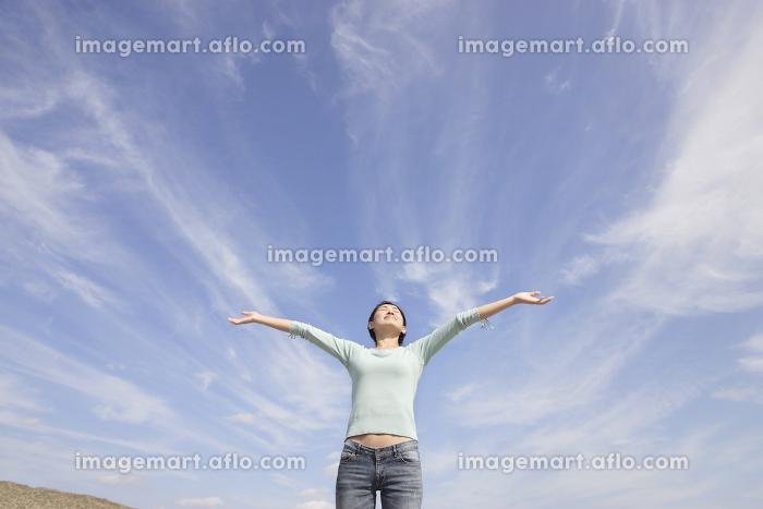 青空の下で両手を広げて深呼吸する女性の販売画像