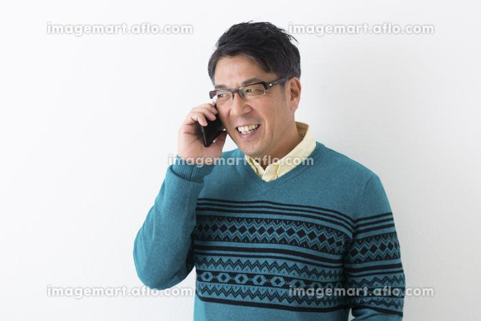 スマホで話すミドル男性の販売画像