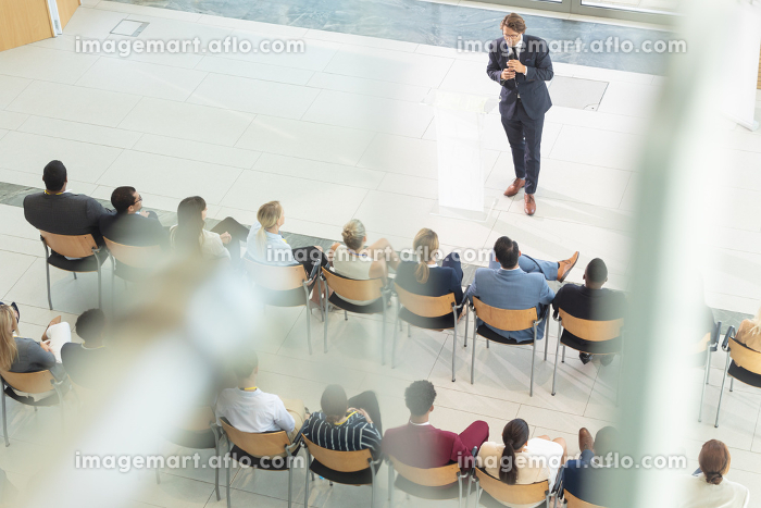 Overhead view of diverse executives sat in conference room, looking speechの販売画像