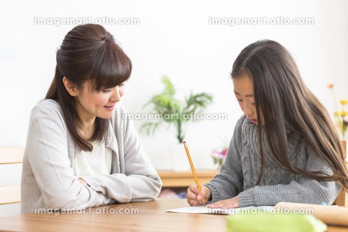 勉強する子供と勉強を見る親