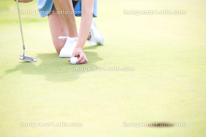 Low section of woman placing ball at golf courseの販売画像