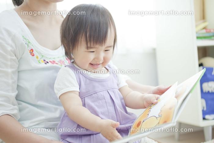 母親に絵本を読んでもらう女の子