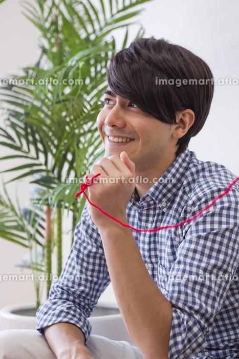 赤い糸で繋がれた男性の販売画像