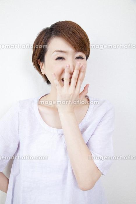 口に手をあて笑うミドル女性