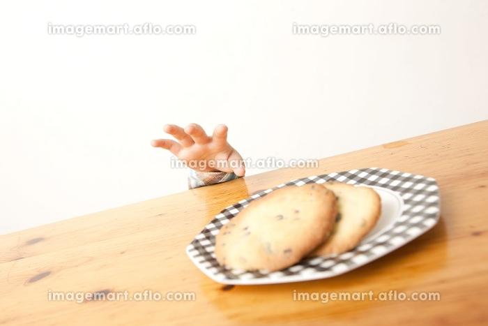 テーブルの上のクッキーを取ろうとする男の子の手元の販売画像