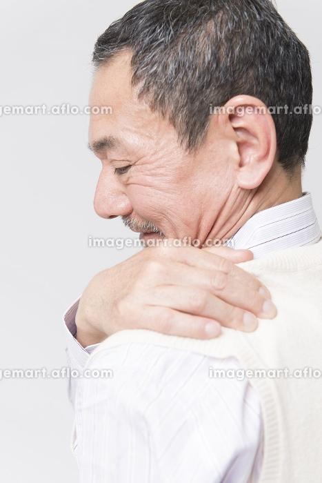 肩こりを訴えるシニア男性