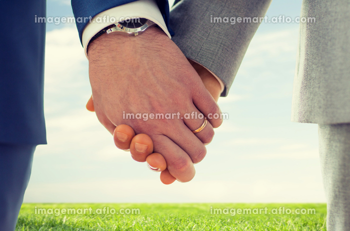 close up of male gay hands with wedding rings onの販売画像