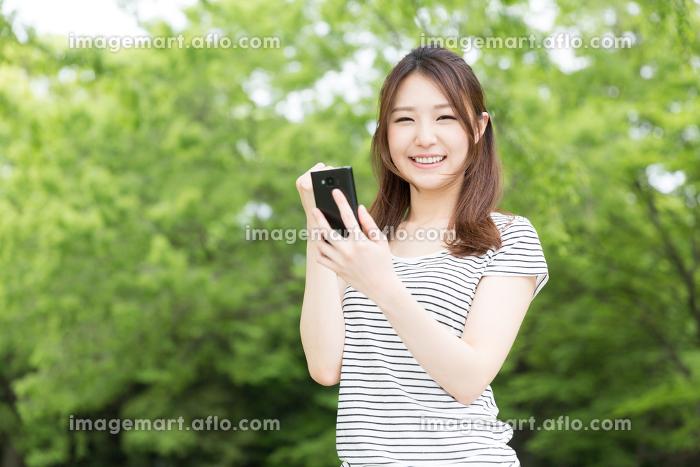 スマートフォンを見る女性 屋外の販売画像