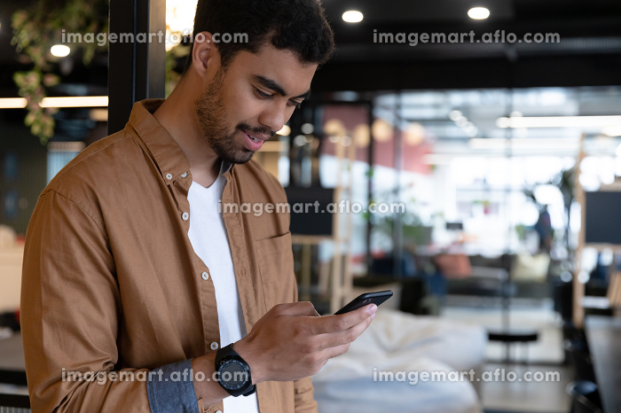 Smiling mixed race businessman texting on smartphone in creative office. social distancing in business office workplace during covid 19 coronavirus pandemic.の販売画像