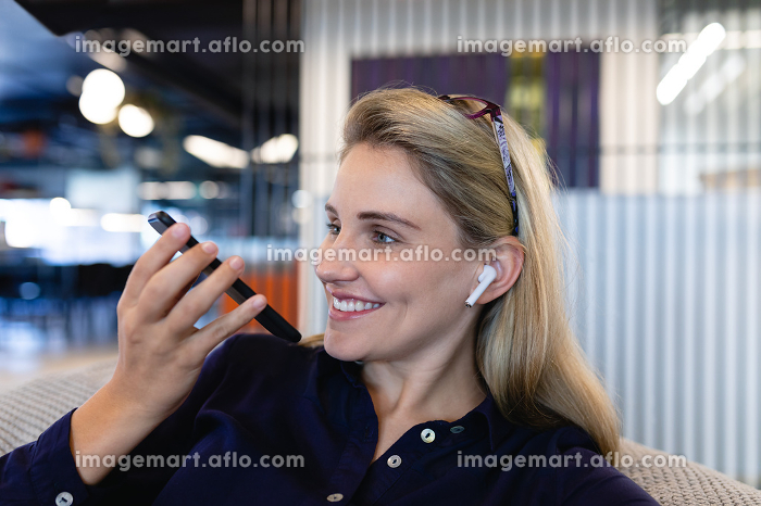 Side view close up of a Caucasian businesswoman wearing smart clothes and earphones, working in a modern office, sitting on a bean bag and talking on the smartphone.の販売画像