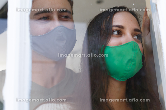 Caucasian couple wearing face masks looking out of window smiling. self isolation at home during covid 19 coronavirus pandemic.の販売画像