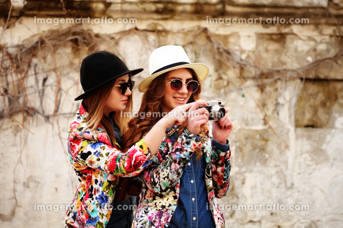 Two female friends taking picturesの販売画像