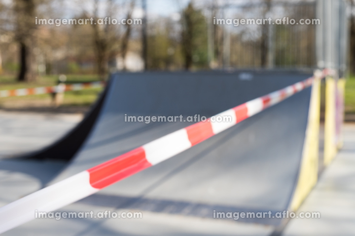 Corona virus COVID-19 restriction. No people due to quarantine. Closed urban skate park. Empty park and playground. Stay at home compaign. Red warning tape on ramps and slides. Social distancingの販売画像