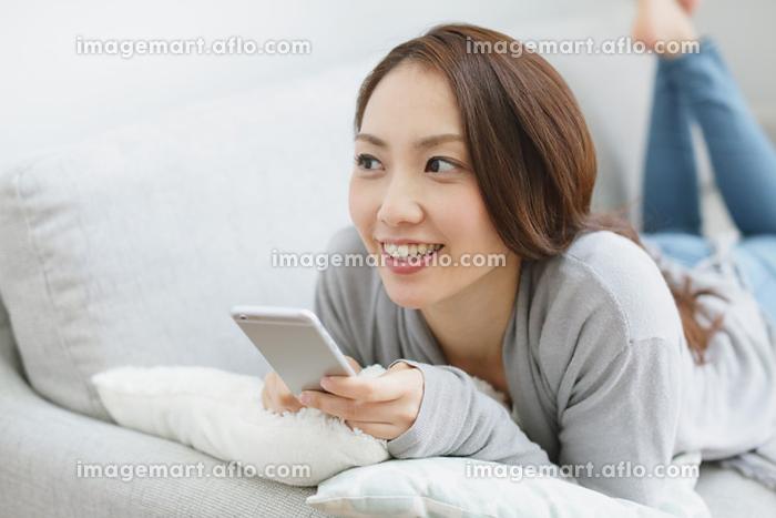 ソファーでスマートフォンを操作する日本人女性